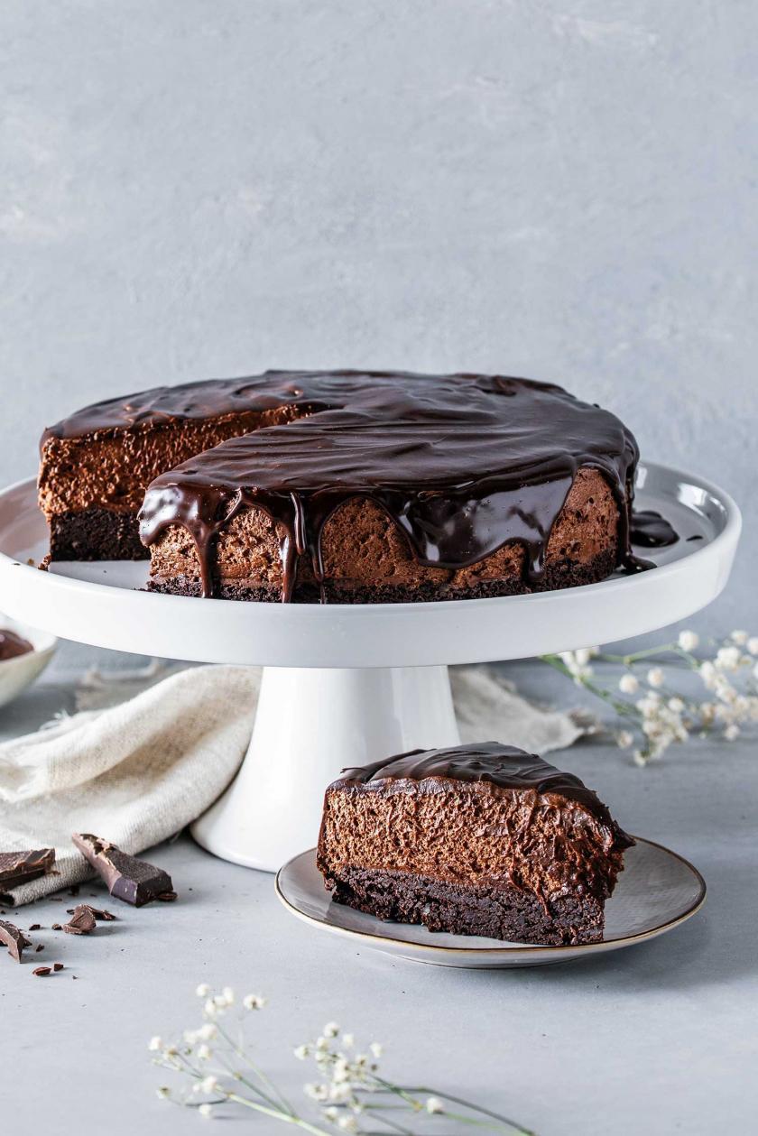 Schokomousse-Torte angeschnitten auf einer Kuchenplatte, davor ein Stück Torte auf einem Teller.