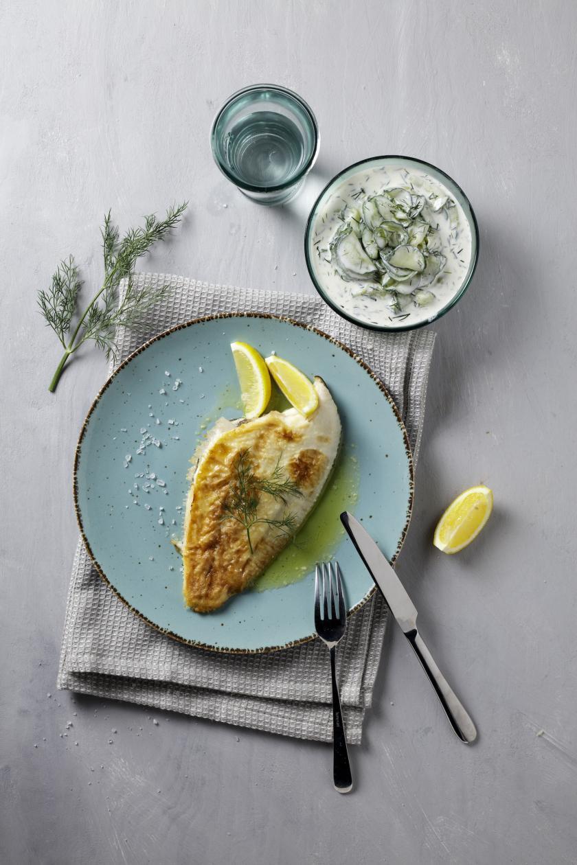 Gebratene Scholle mit Zitrone auf einem Teller, daneben Gurkensalat.