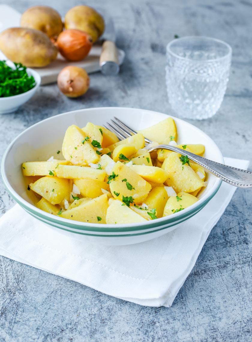 Schwäbischer Kartoffelsalat auf einem Teller auf einem gedeckten Tisch.