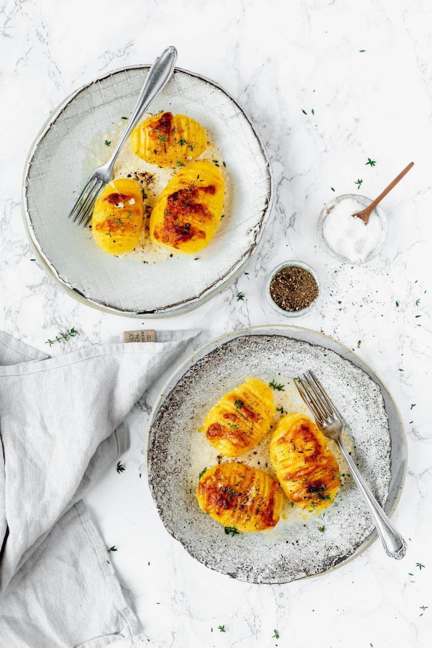 Schwedische Kartoffeln auf zwei Tellern auf gedecktem Tisch.