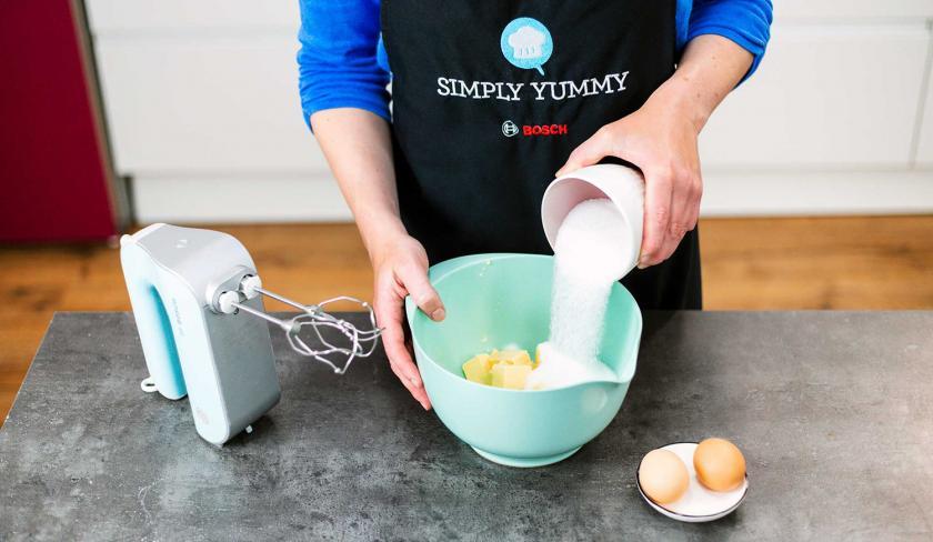 Zucker wird zu Butter in eine Rührschüssel gegeben.