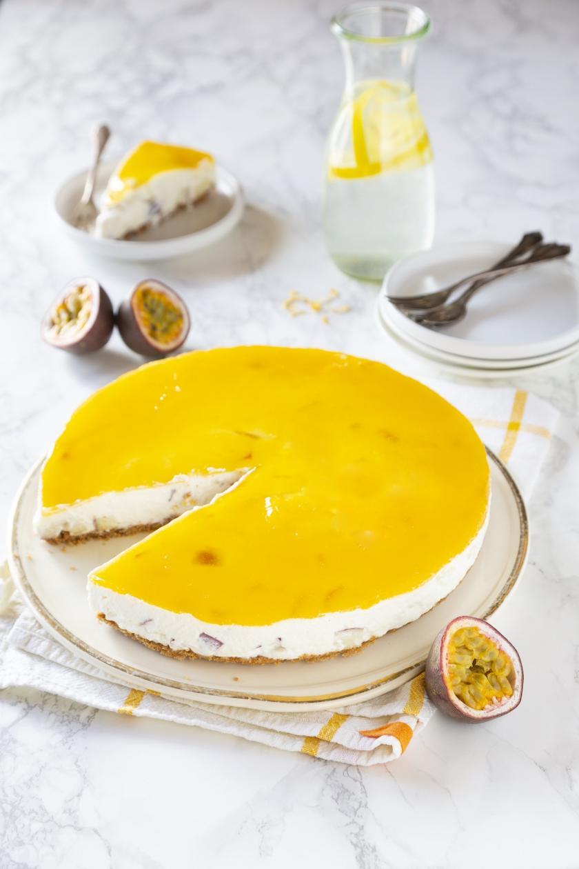 Solero-Torte ohne Backen angeschnitten auf einer Kuchenplatte, daneben Maracujas.