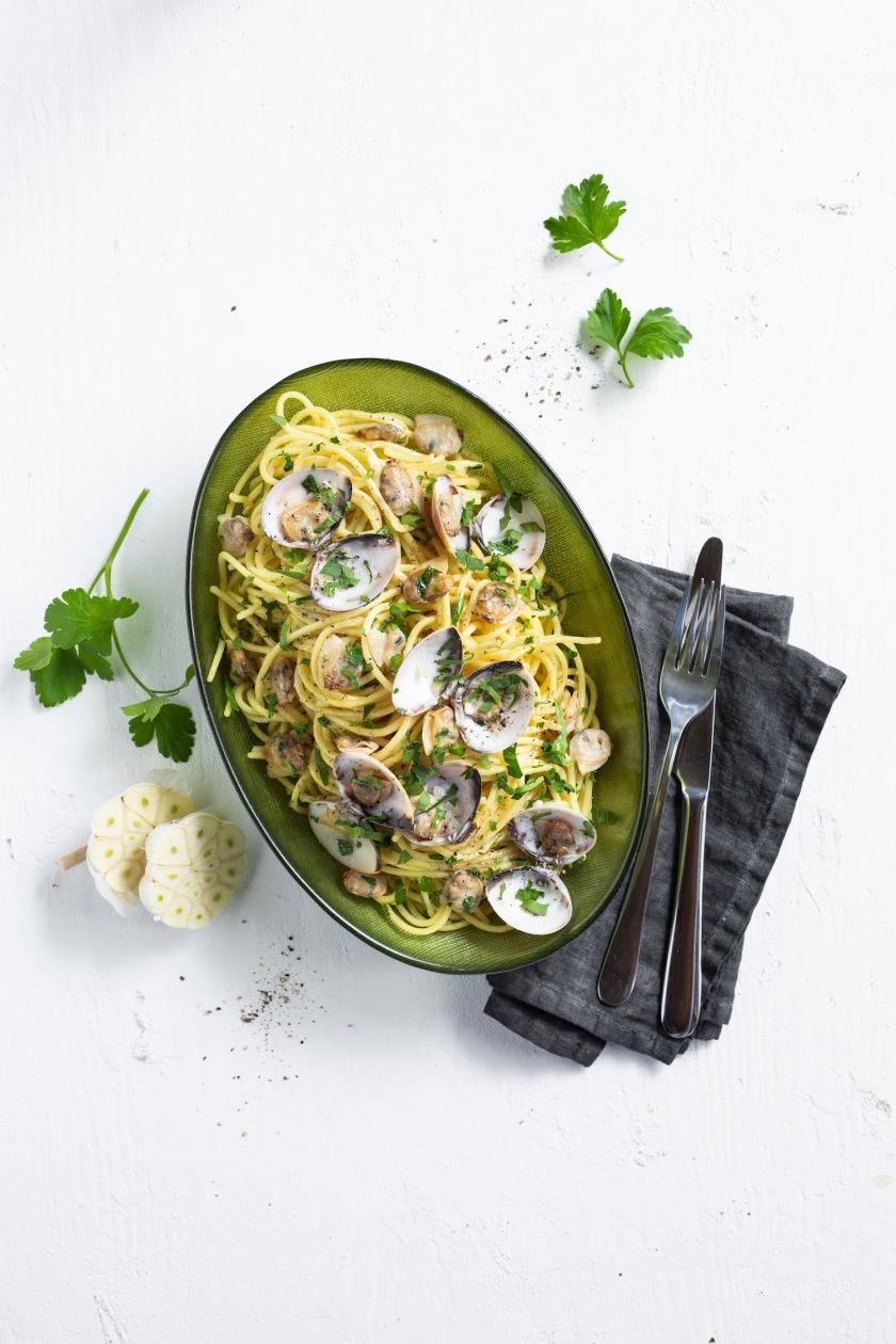 Spaghetti Vongole in einem Pastateller angerichtet mit Knoblauch und Petersilie.