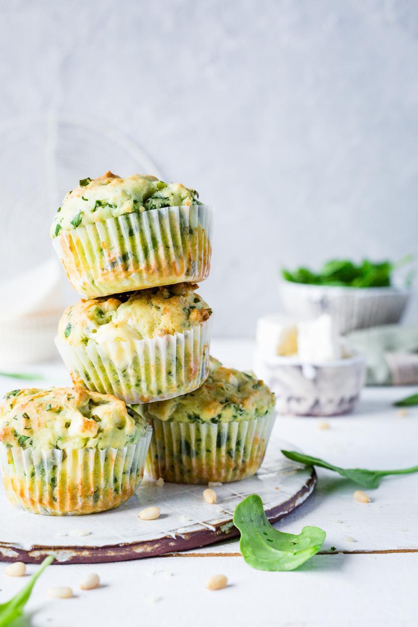 Spinat-Feta-Muffins übereinandergestapelt auf weißem Holztisch.