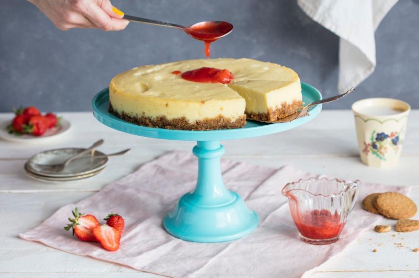 Angeschnittener Strawberry Cheesecake auf einer Etagere wird mit einem Löffel Erdbeersauce garniert.