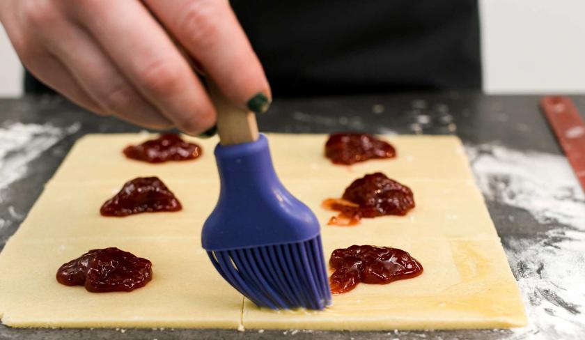 Der Teig für süße Knallbonbons wird mit Ei eingestrichen.