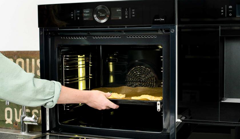 Ein Blech süße Knallbonbons wird in den Ofen geschoben.