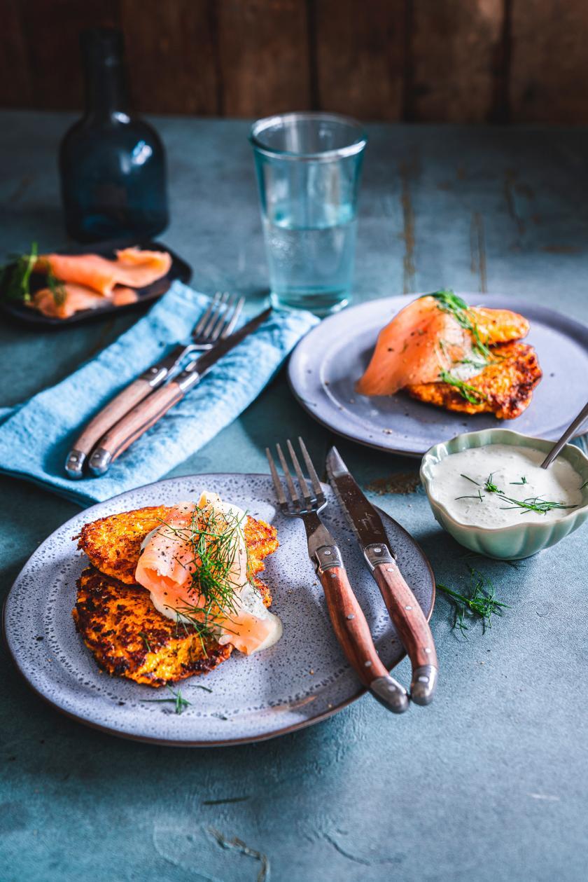 Süßkartoffelpuffer mit Lachstopping auf einem Teller.