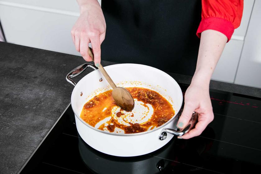 Für die Thai Curry Basis wird Currypaste in einem Topf angebraten.