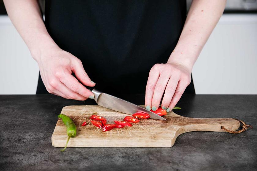 Für zusätzliche Schärfe im Thai Curry werden Chilis geschnitten.