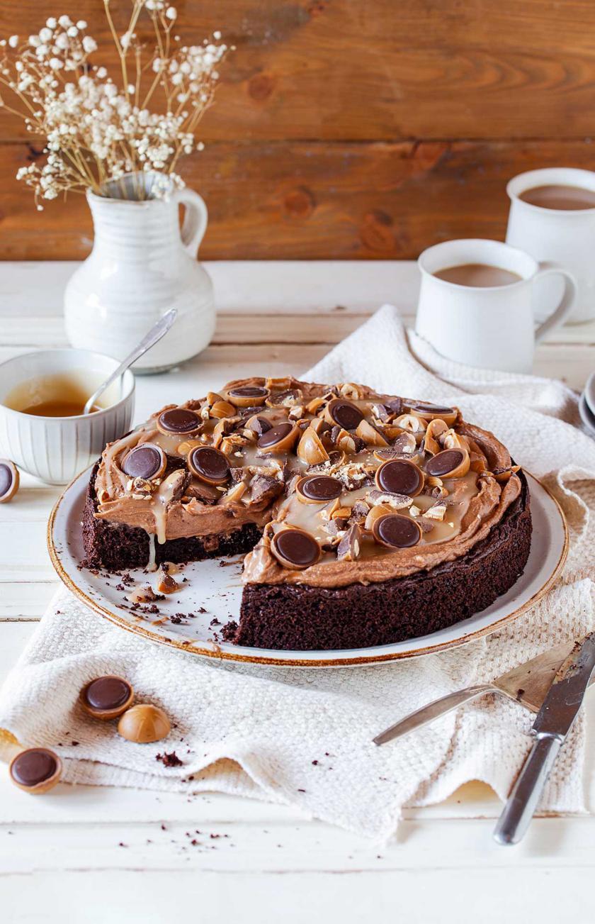 Toffifee-Torte angeschnitten auf einer Kuchenplatte.