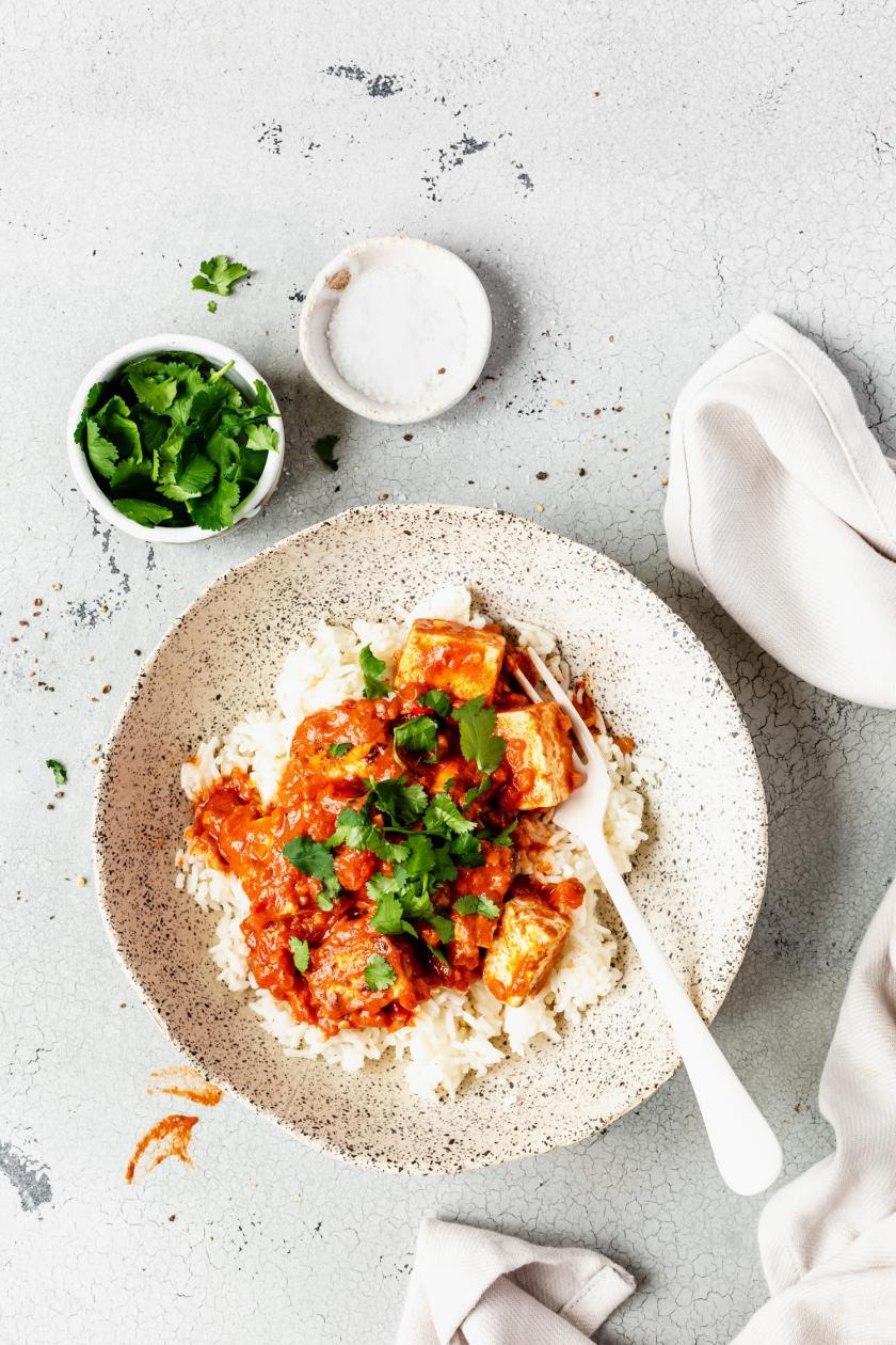 Tofu Tikka Masala mit Reis und Koriander auf einem Teller.