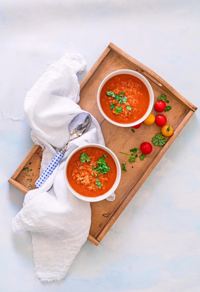 Tomatensuppe mit Reis in zwei Schüsseln auf einem Tablett.
