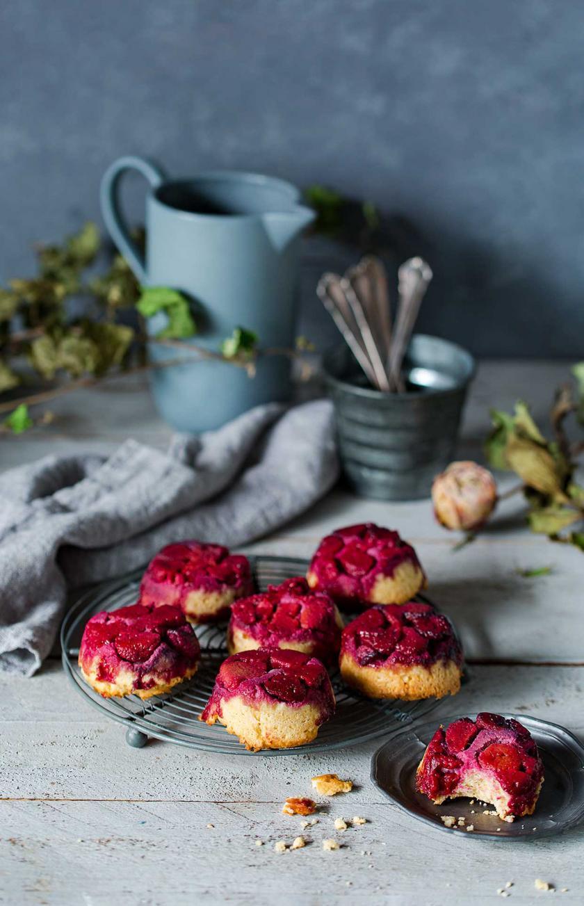 Mehrere Upside Down Low Carb Muffins auf einem Teller auf einem gedeckten Tisch.