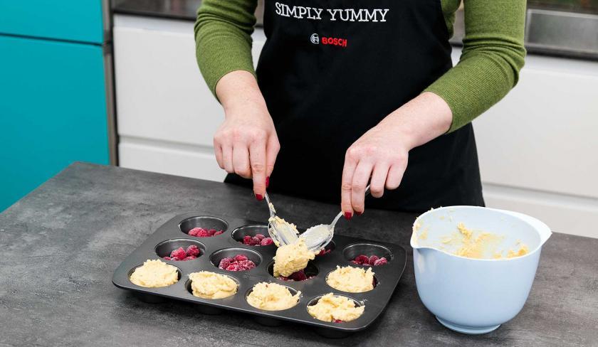 Der Teig für die Upside Down Low Carb Muffins wird auf die Muffinmulden verteilt.