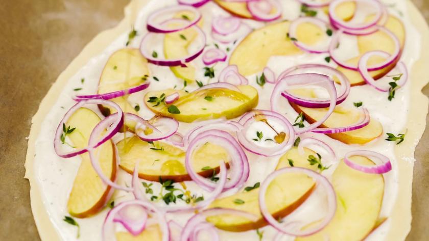Flammkuchen vegan mit Apfel und Zwiebel belegt.