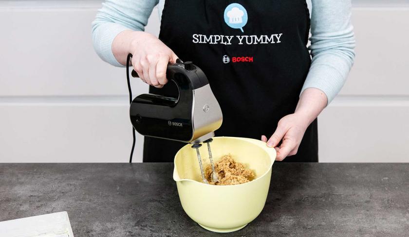 Der Teig für veganer Pflaumenkuchen wird in einer Rührschüssel mit einem Handmixer geknetet.