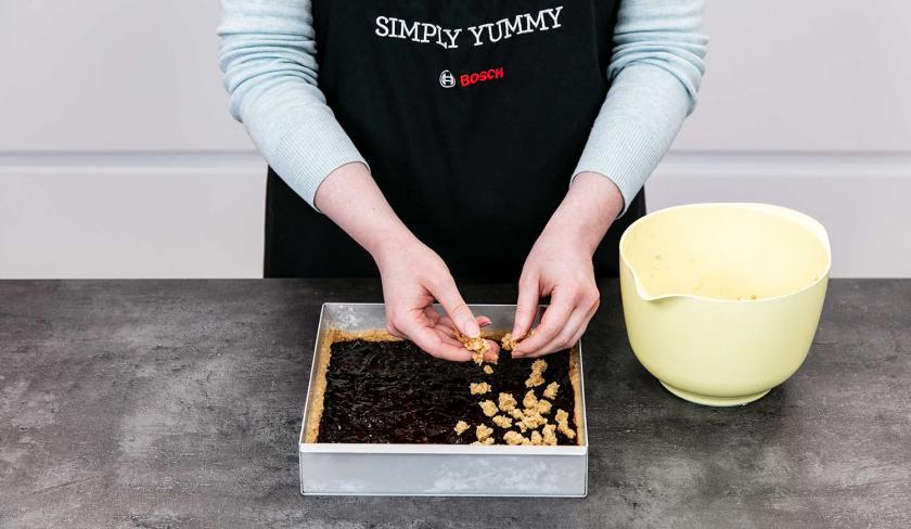Auf den veganen Pflaumenkuchen werden Streusel verteilt.