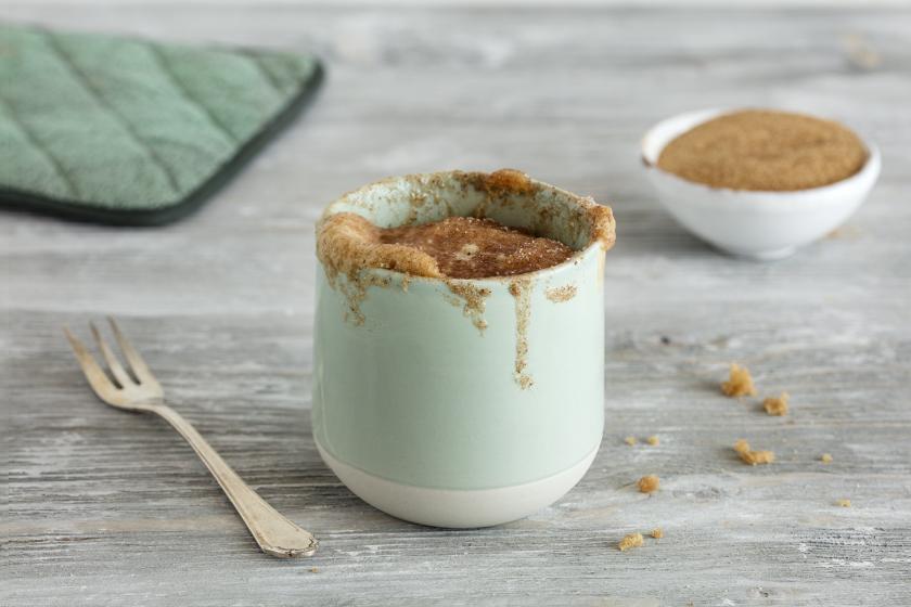 Ein Tassenkuchen ohne Ei und mit braunem Zucker steht auf einem Holzuntergrund. Daneben liegt eine Gabel.