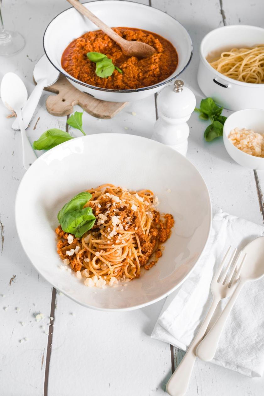 Spaghetti mit Bolognese im Teller und dahinter eine Schüssel mit vegetarischer Bolognese