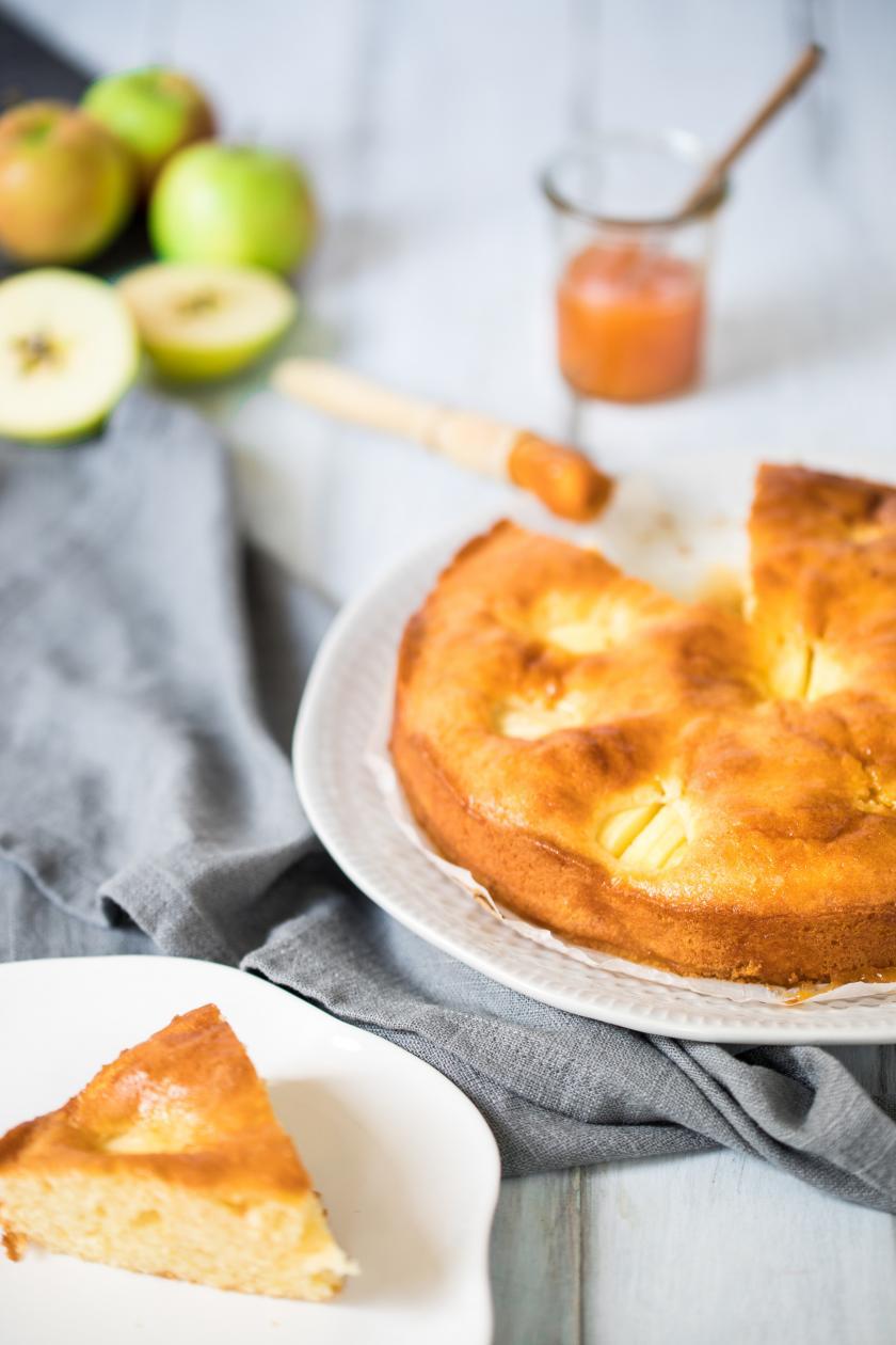 Versunkener Apfelkuchen liegt angeschnitten auf einer Etagere und ein Stück daneben auf einem Teller.