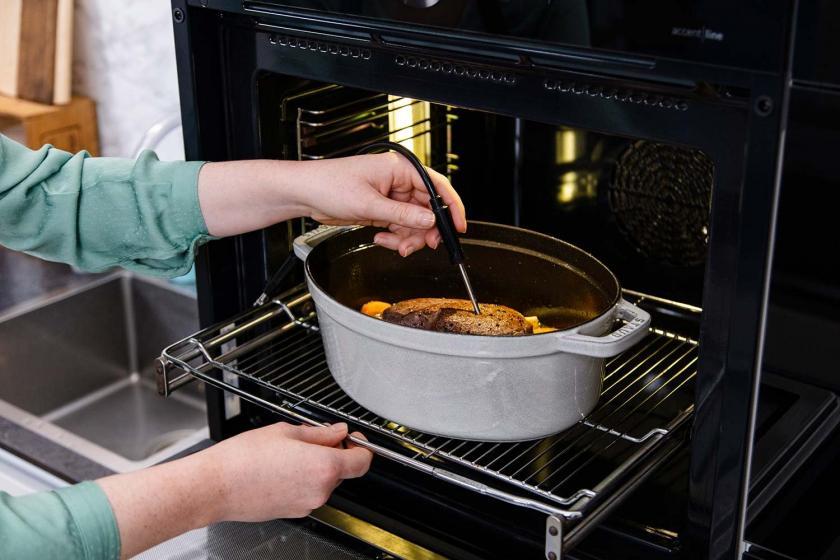 Fleisch mit Bratenthermometer im Bräter im Ofen.