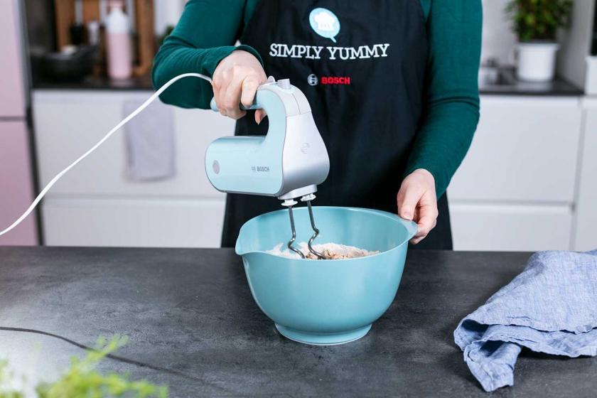 Der Teig für die Vollkornbrötchen wird mit einem Handmixer geknetet.