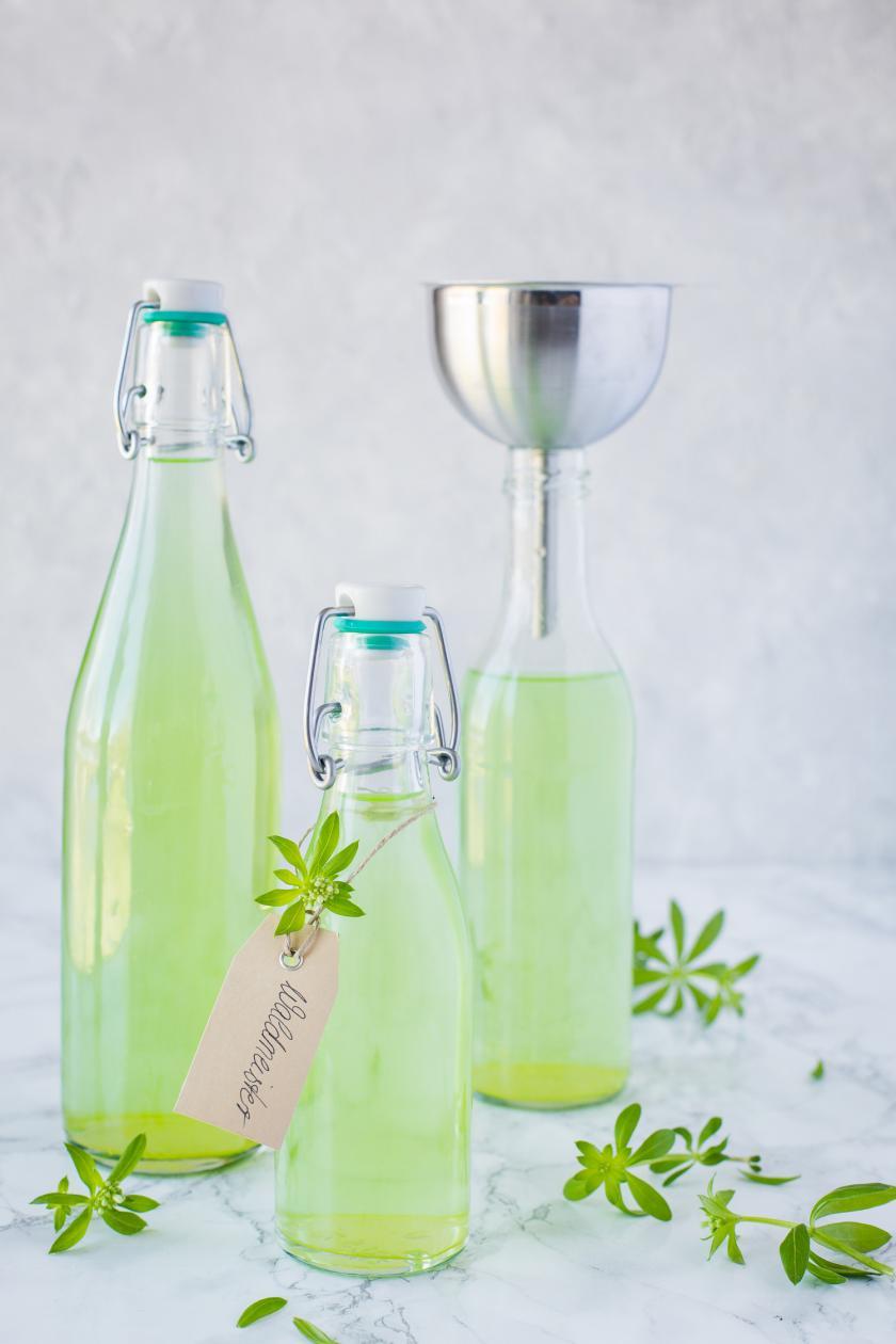 Drei Flaschen Waldmeistersirup mit Trichter und Etikett.