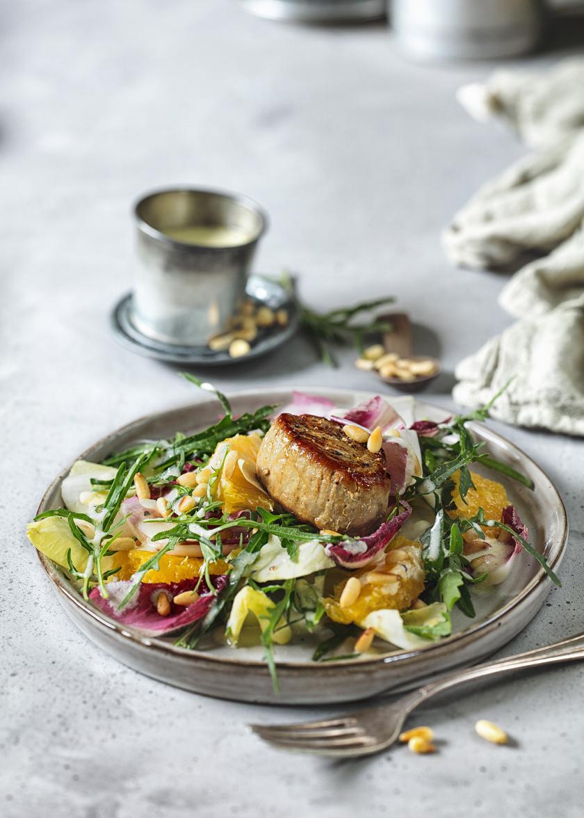 Wintersalat mit Orangen und Schweinefilet auf einem Teller angerichtet.