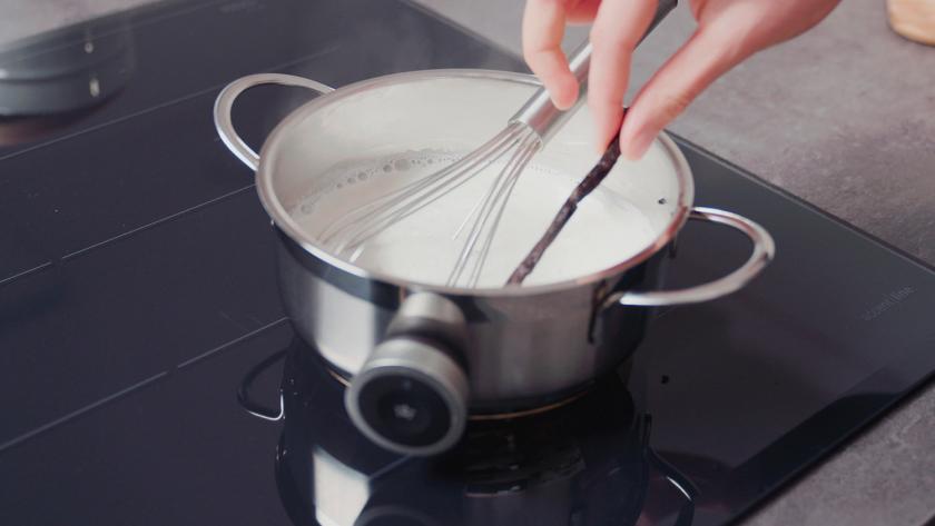 Vanilleschote wird aus einem Topf mit Milch entfernt.