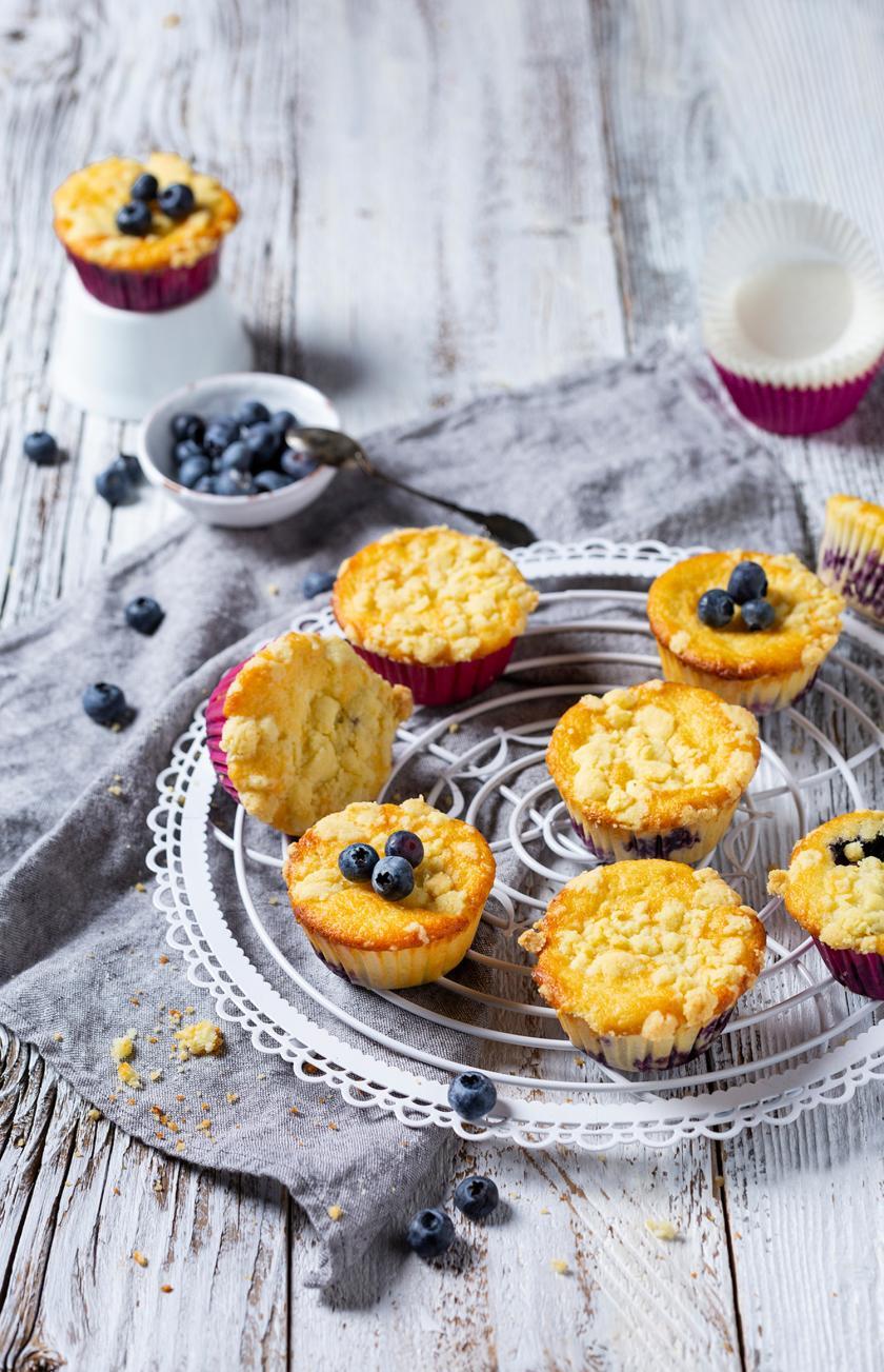 Viele Zitronen-Blaubeermuffins mit Streuseln auf einem Kuchengitter.