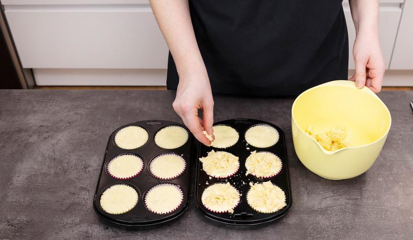 Die Zitronen-Blaubeermuffins werden mit Streuseln bedeckt.