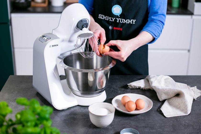 Eier werden in die Rührschüssel einer Küchenmaschine gegeben.