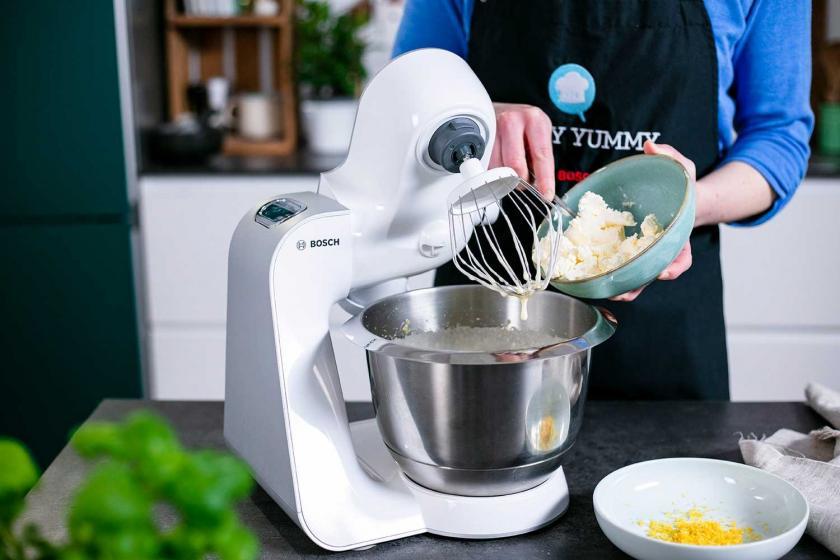 Frischkäse wird in die Rührschüssel einer Küchenmaschine gegeben.