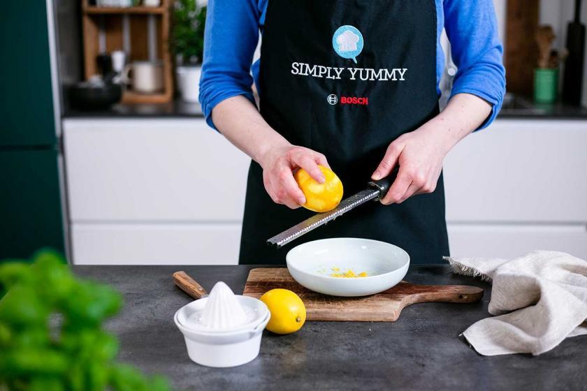 Zitronenschale wird über einem Teller abgerieben.