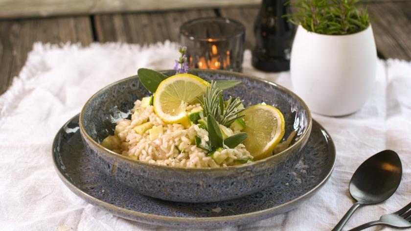 Zucchini-Risotto mit Zitronen dekoriert in dunkler Schale auf gedecktem Tisch.