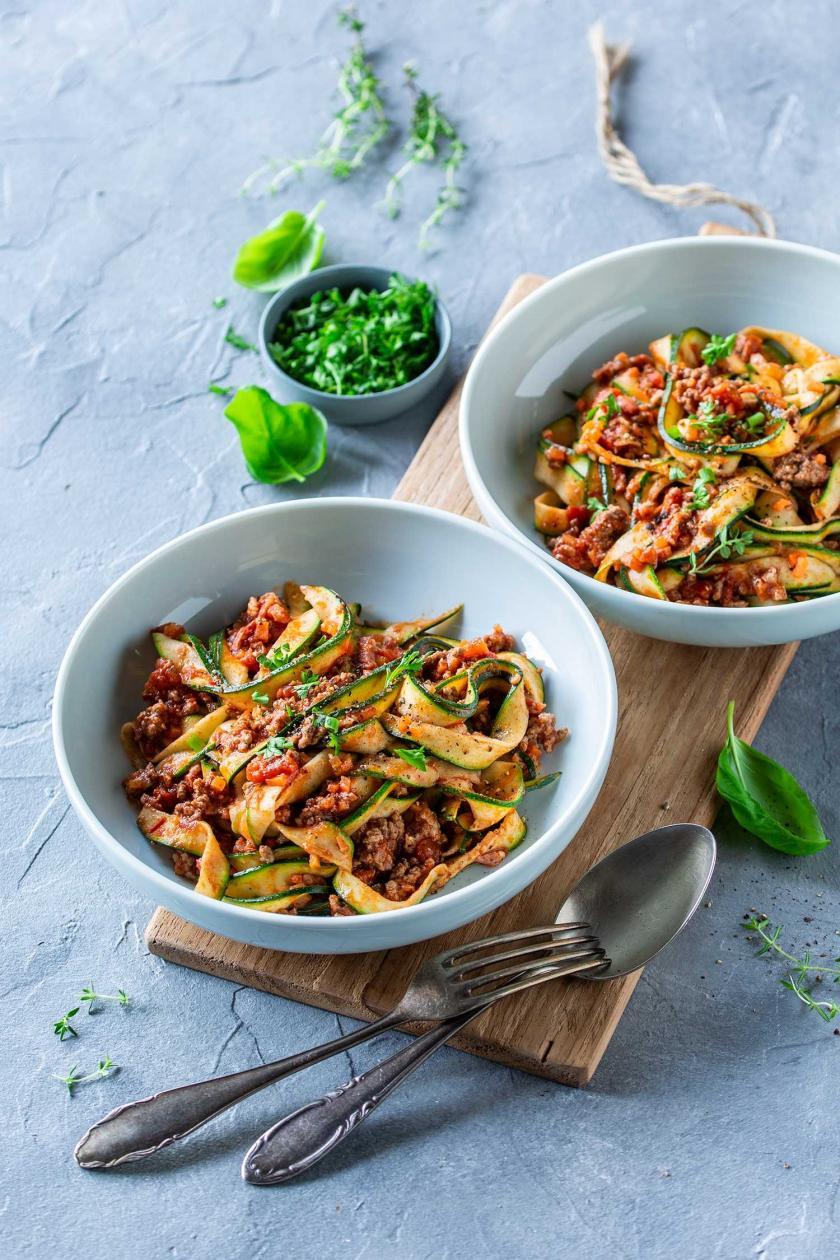Zucchini Spaghetti Bolognese auf zwei Tellern angerichtet auf einem Holzbrett mit Besteck.