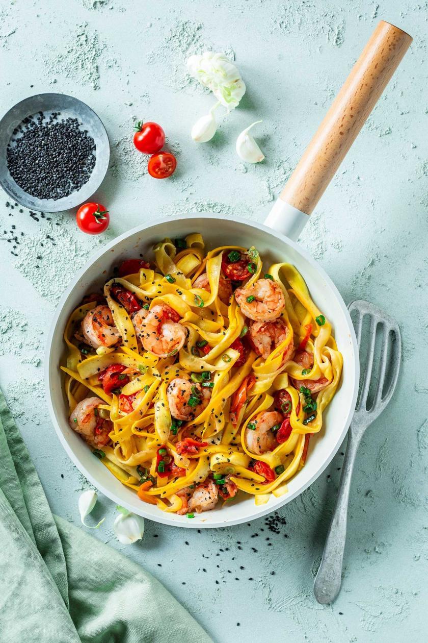Zucchini Spaghetti mit Garnelen in einer Pfanne.