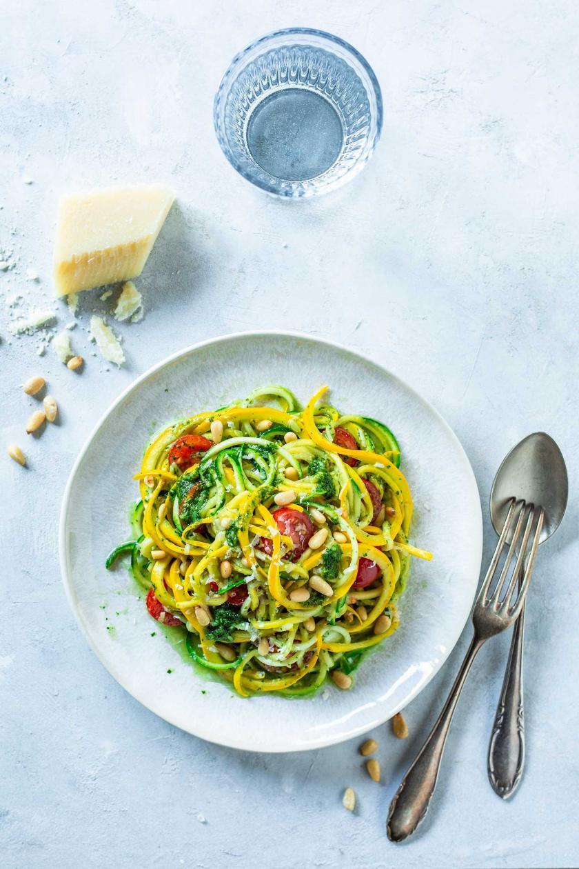 Zucchini Spaghetti mit Pesto auf einem Teller angerichtet, daneben Besteck und Parmesan.