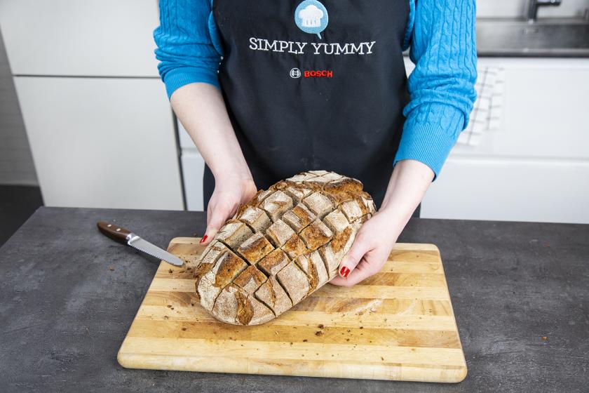 Für ein gefülltes Brot wird der eingeschnittene Laib vorsichtig aufgebrochen.