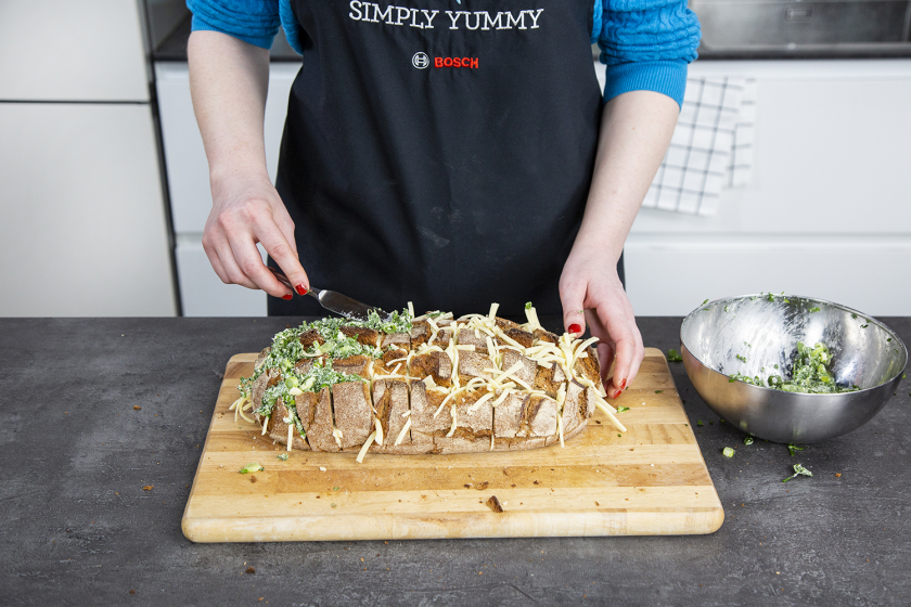 Für das gefüllte Brot wird der Laib mit Kräuterbutter gefüllt.