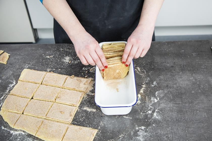 Der Teig für das Zupfbrot wird in eine Kastenform aufrecht geschichtet.