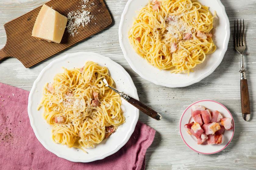 Spaghetti Carbonara auf zwei Tellern, daneben Parmesan und Speck.