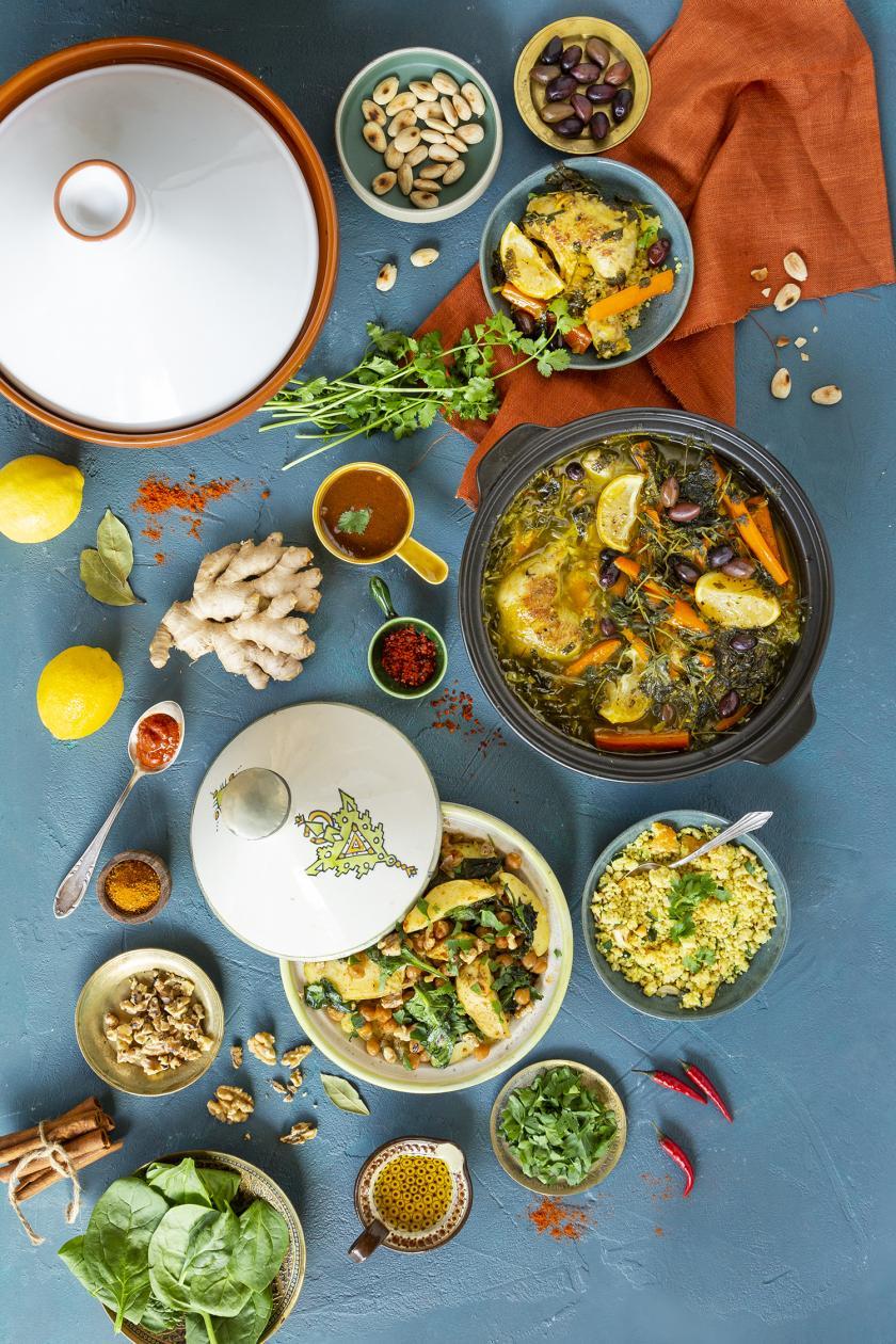 Mehrere Tajine und Zutaten auf einem Tisch verteilt.