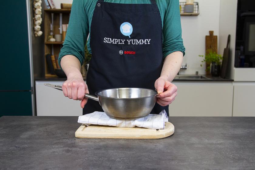 Tofu eingewickelt in einem Tuch wird mit einer Pfanne beschwert.