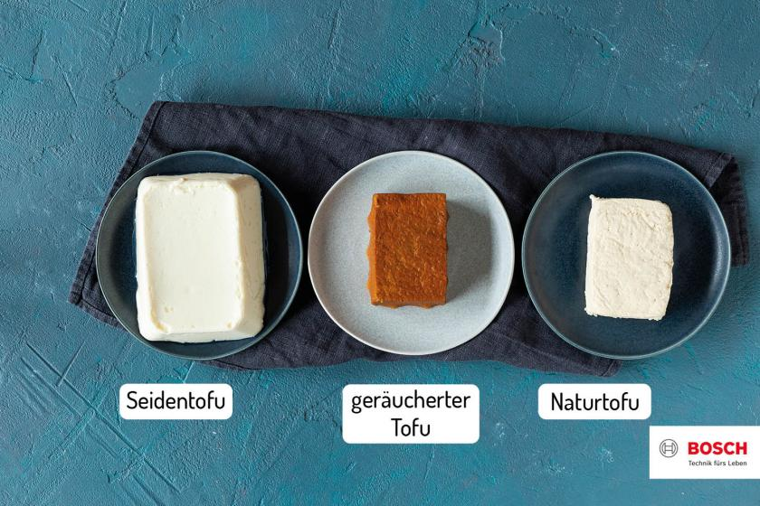 Drei verschiedene Tofu-Sorten nebeneinander auf Tellern.