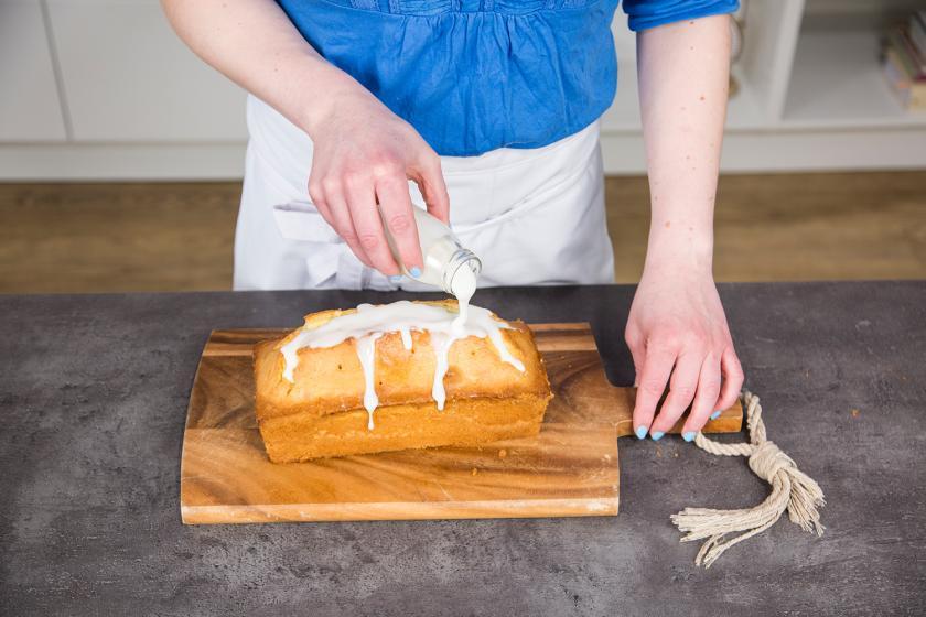 Ein Zitronenkuchen wird mit Zuckerguss übergossen.